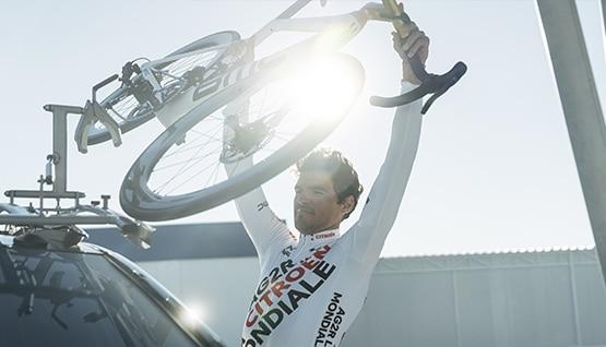 Coureur de l'équipe AG2R CITROËN TEAM installant son vélo sur le porte-vélos